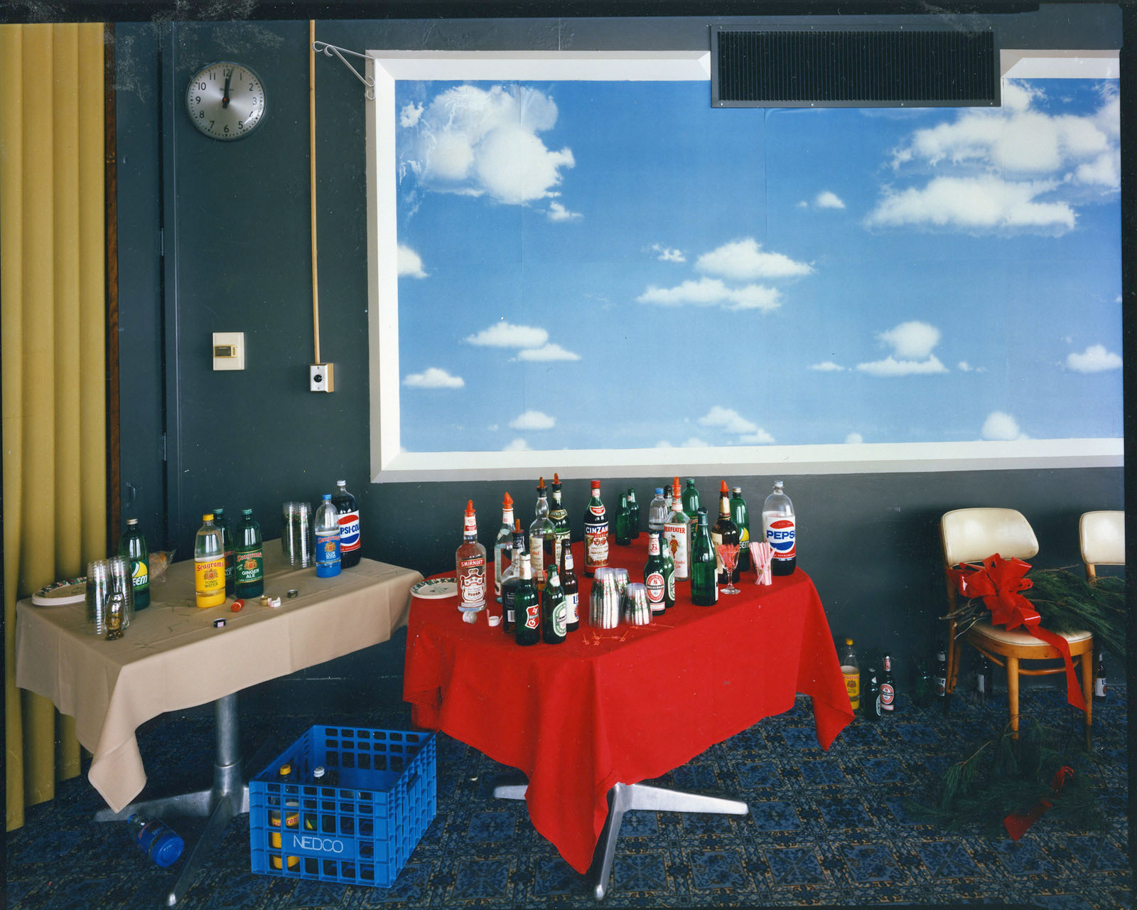 Framed clouds with blue sky, over 2 tables with soda/liquor bottles (red and tan tablecloths)